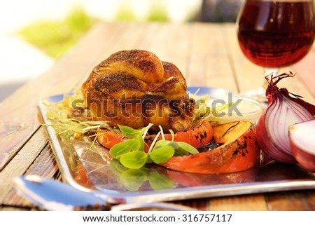 Roasted chicken with pumpkin on a plate outside