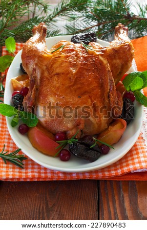 Roasted Christmas whole chicken with prunes and apples over white wood background