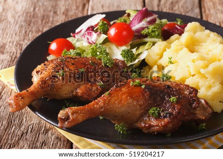 roasted duck leg with mashed potatoes garnish and salad mix close-up on a plate. Horizontal