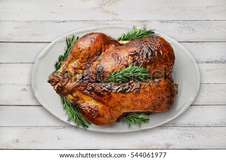 Roasted duck with rosemary on white wooden planks.