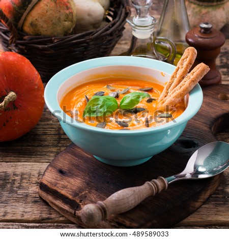 Roasted pumpkin and carrot soup with cream and pumpkin seeds on rustic wooden background.