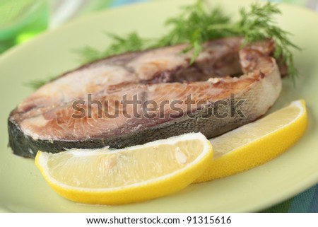 Roasted tuna steak with lemon and dill on a plate closeup