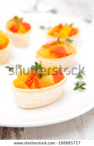 roasted vegetables with thyme in tartlets on the plate, vertical