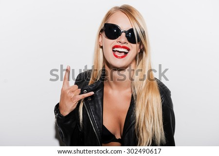 Rock and roll! Joyful young woman in black bra and leather jacket looking at camera and gesturing while standing against white background