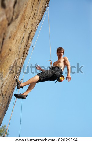 rock climber climbing an overhanging cliff against the blue sky
