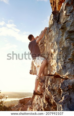 Rock climber climbing up a steep piece of mountain with copyspace
