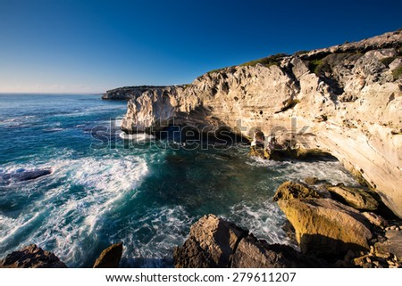 Rocky cove with ocean wave crashing into an eroded arch
