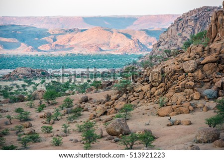 Rocky landscape of Kunene Region at Namibian winter with huge boulders and green trees