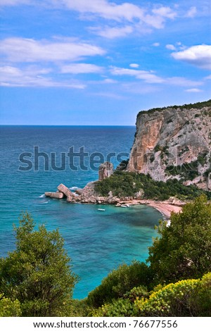 rocky shore Sardinia Italy blue sea and sky and high cliffs vacation landscape mountains and ocean