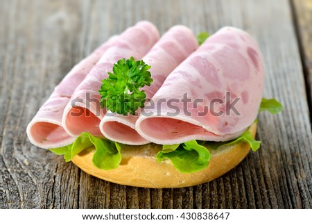 Roll with sliced ham sausage and lettuce leaf served on a rustic wooden table