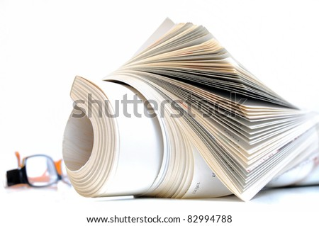 Rolled up magazine with white cover and glasses in background