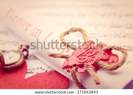 Rolled up scroll of love letter fastened with natural brown jute twine hemp rope, sealed with sealing wax and stamped with alphabet letter B. Decorated with a red mulberry paper heart and pocket watch