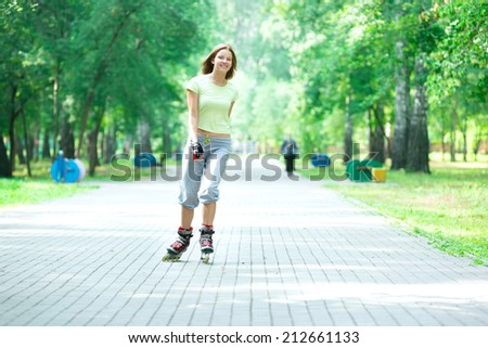 Roller skating sporty girl in park rollerblading on inline skates.  Caucasian woman in outdoor fitness activities.