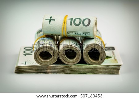 rolls and stack of banknotes - polish zloty - 100 pln