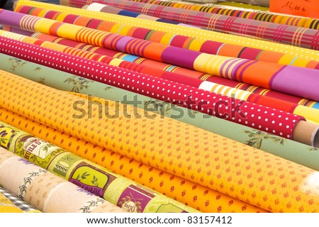 Rolls of colourful fabric at a market