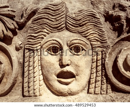 Roman theatrical mask or goddess in Greek mythology. Ancient mask in a Greek theatre, relief on stone wall. Decoration of theater for tragedy performance, classic art and Antique culture of Europe.