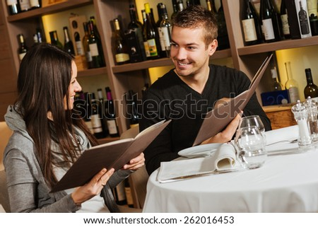 Romantic couple at a restaurant looking at the menu