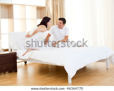 Romantic couple finding out pregnancy test sitting on the bed
