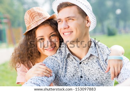 romantic couple lying on the grass in the summer park, spending time with loved ones