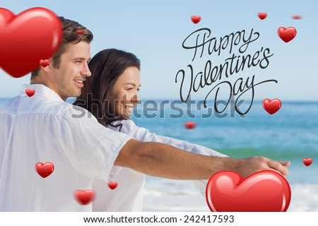 Romantic couple relaxing on the beach against happy valentines day