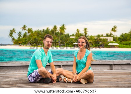 Romantic Couple sitting on the pier on a tropical island