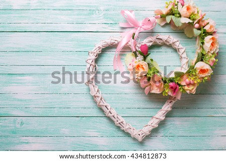 Romantic or wedding background. Flower wreath and decorative heart  on turquoise  wooden background. Selective focus. Place for text.
