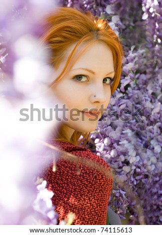 Romantic portrait of beautiful young redhead girl among spring lilac flowers.
