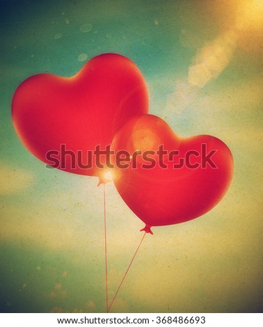 Romantic red balloons in a shape of a heart, grunge paper textured.