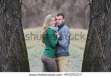 Romantic teenage couple between two big trees in autumn park