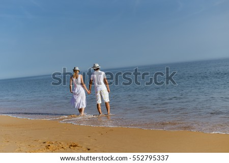 Romantic travel vacation. Joyful male and female couple lovers walking on sand beach sunny outdoors background