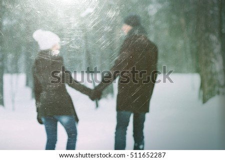 Romantic walk in love couple. Winter day in park. Photo in defocusing. Effect of old photos from scuffs and scratches