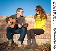 Romantic young couple portrait playing guitar under blue sky. - stock photo