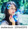 romantic young girl inflating colorful soap bubbles in park - stock photo