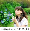 romantic young girl inflating colorful soap bubbles in spring park - stock photo
