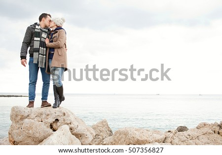 Romantic young tourist couple together on textured rocks in a destination beach on a winter holiday with coats, kissing being romantic, hugging outdoors. Travel lifestyle, coastal exterior space.