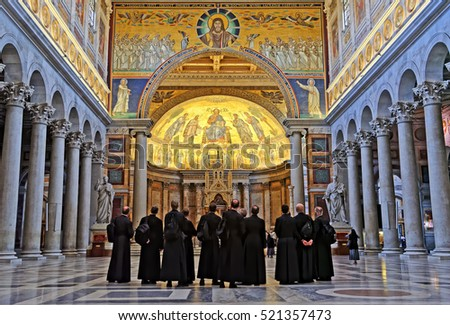 Rome, Italy - August 17, 2016: Basilica of Saint Paul Outside the Walls. Famous apse mosaic of Jesus Christ Pantokrator from 1220 AD and Catholic priests, Rome, Italy