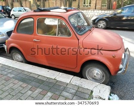 ROME, ITALY - CIRCA OCTOBER 2015: red FIAT 500 car parked in a street of the city centre