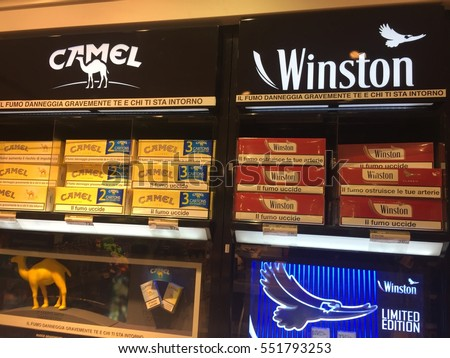 Rome, Italy - December 24, 2016: Winston and Camel cigarette display with packaging warning messages: Smoking seriously harms you and others around you. Winston and Camel are brands of cigarettes