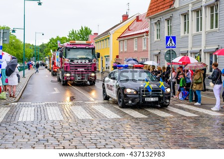 Ronneby, Sweden - June 10, 2016: 2006 police painted Dodge Charter leading the student truck and tractor parade through town on this rainy day.