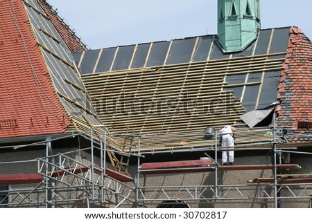Roof construction works. Worker and scaffolding. Building renovation.