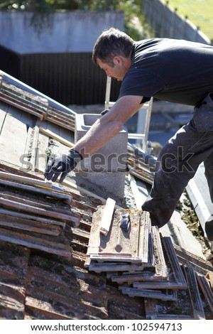 Roofer repairing a badly damaged roof