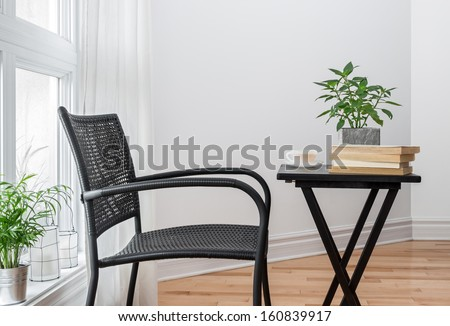 Room with black chair and table, decorated with plants.