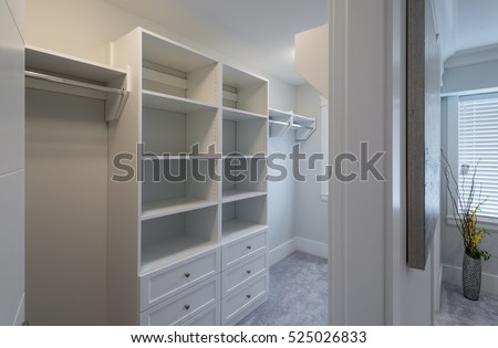 Room with the open empty closet, working closet, cupboard with some racks, hangers and big mirror. Interior design.