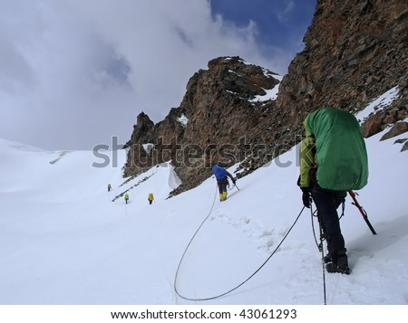 Roped team of mountaineers approaching a mountain pass.