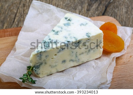 Roquefort cheese with thyme and dry apricot on the wood background