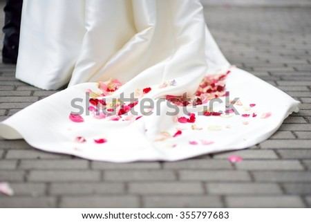Rose petals on a wedding dress after wedding ceremony