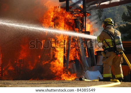 ROSEBURG, OR - SEPTEMBER 03: Single fire fighter sprays a straight steam into a fully involved shop fire off of Breezy Lane, September 03, 2011 in Roseburg, OR