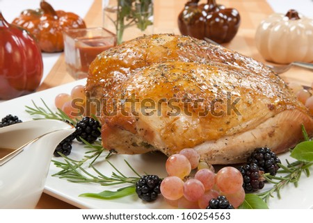 Rosemary-basil rub roasted turkey breast garnished with grapes, blackberies, and fresh basil, and rosemary in fall themed surrounding.