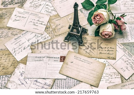 roses, antique french postcards carte postale and souvenir Eiffel Tower from Paris. nostalgic holidays background. retro style toned picture