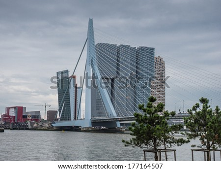 ROTTERDAM, NETHERLANDS - 17 AUGUST 2013: Erasmusbridge, also known as The Swan, and in the background the largest building of the Netherlands, designed by architect Rem Koolhaas